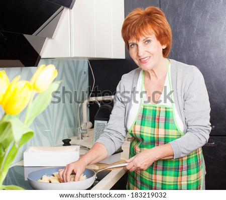 Female cooking at kitchen. Woman preparing pasta