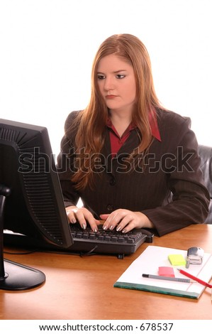 Female corporate executive typing at the computer in her office