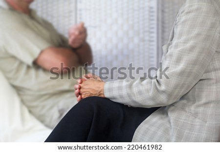 Female Counseling therapist in foreground listening to male patient sat on couch with client being soft focus in background - stock photo