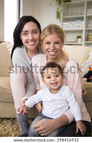 Female couple sit together with their son in their home and all smile for the camera - stock photo