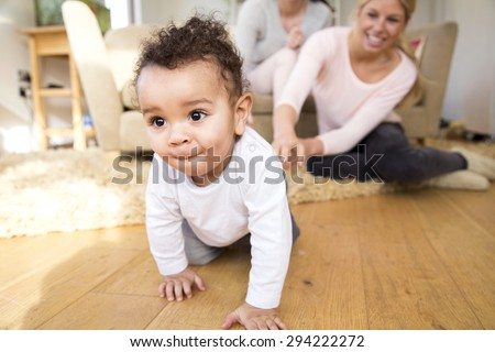Female couple watch proudly as their baby son crawls along the floor - stock photo
