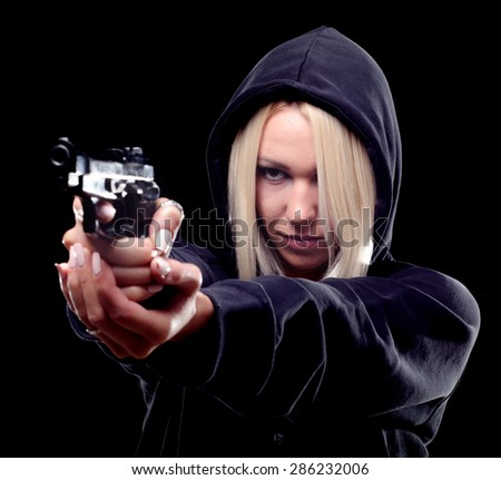 Female criminal with hood on her head shooting with gun on the street at night.