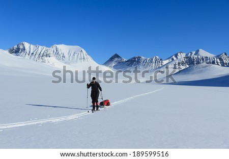 Female cross country skier with polka (sled) in the snow in Lapland, Sweden.