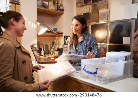 Female customer being served at the counter of a record shop - stock photo