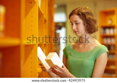 Female customer in pharmacy comparing two medications - stock photo