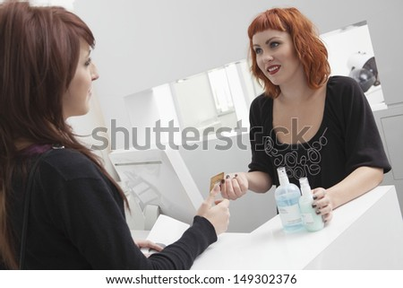 Female customer looking at owner while paying for hair products through credit card in salon - stock photo