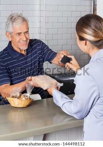 Female customer making credit card payment at cash counter while receiving product - stock photo