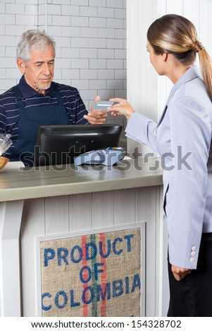 Female customer making payment by credit card at cash counter in supermarket - stock photo