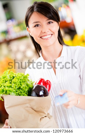 Female customer paying by credit card at the supermarket - stock photo