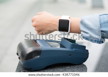 Female customer paying through smart watch by NFC - stock photo