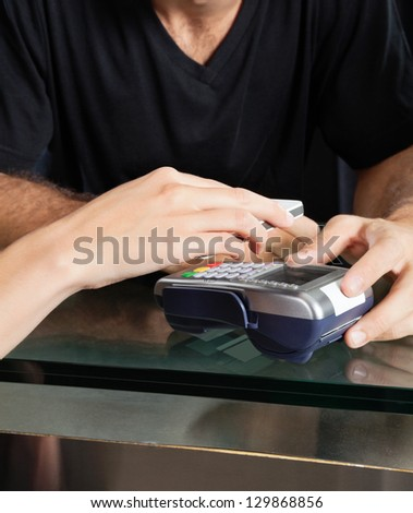 Female customer paying with mobilephone over electronic reader at salon counter