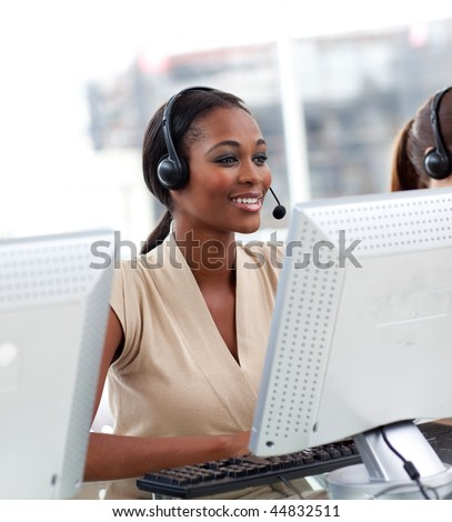 Female customer service agent with headset on in a call center - stock photo