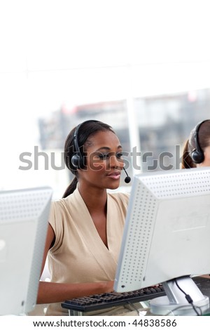 Female customer service agent with headset on working at a computer - stock photo