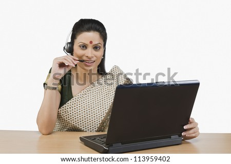 Female customer service representative working on a laptop