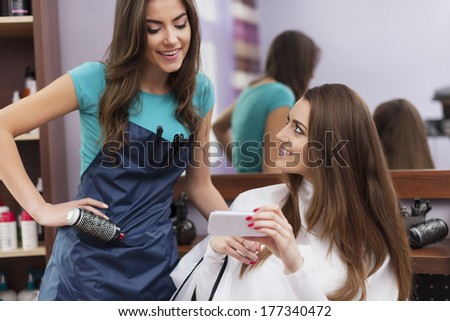 Female customer showing which hairstyle she wants on mobile phone  - stock photo