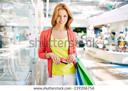 Female customer with plastic card and shopping bags in trade center