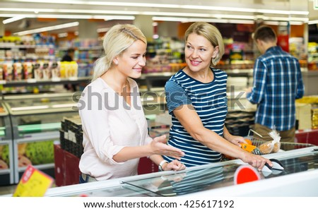 Female customers standing near display with frozen food at a supermarket  - stock photo