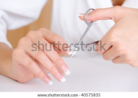 Female cutting nail on the  index finger - unrecognizable person, macro shot