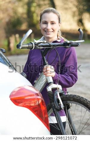 Female Cyclist Taking Mountain Bike From Rack On Car