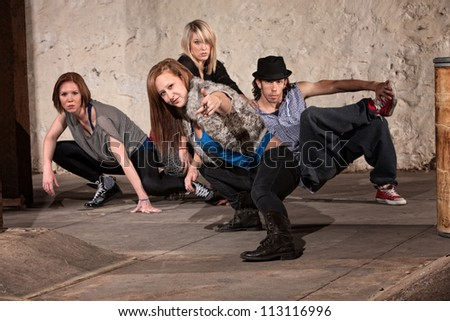 Female dancer and friends posing in underground setting - stock photo