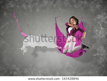 female dancer jumped surrounded by splashes of paint - stock photo