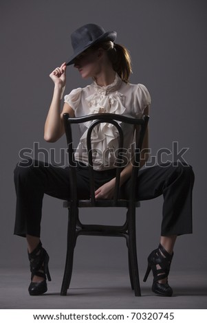 female dancer with hat sitting on the chair over grey background - stock photo