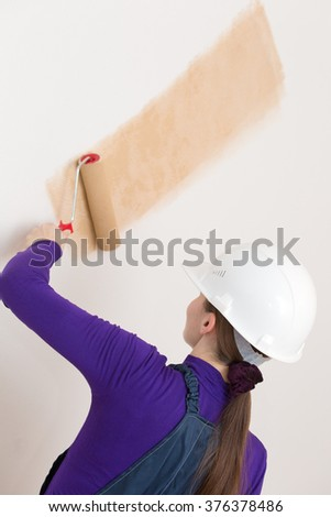 Female decorator or house painter worker painting wallpaper with painting roller tool in new apartment - stock photo