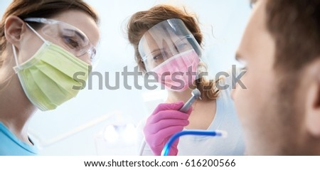 Female dentist and assistant working. Photographed from patient's point of view.