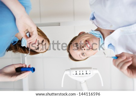 Female dentist and her assistant during dental treatment - stock photo