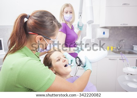 Female dentist and her assistant wearing light blue gloves take jaw x-ray of female brown haired patient over white dental room