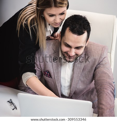 Female discusses work on computer with assistant in an office setting.
