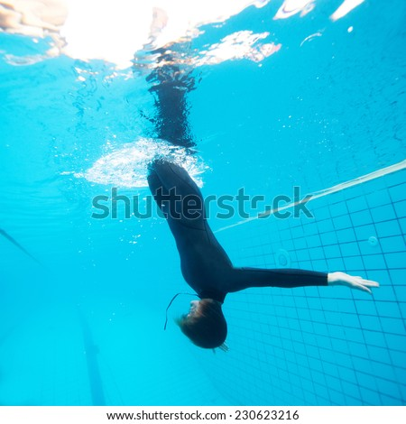 Female diver calmly diving downwards through surface into swimming pool