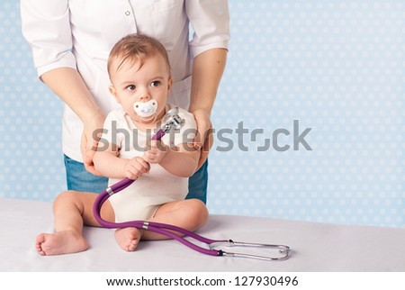 Female doctor and baby patient - portrait - stock photo
