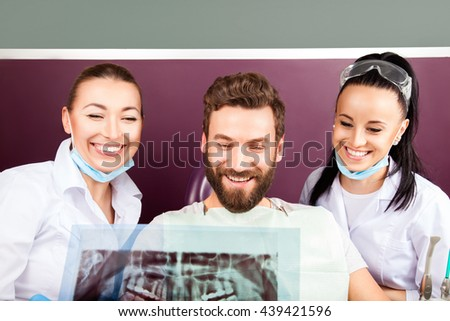 Female doctor and her assistant showing dental x-ray to male patient in stomatological hospital. Handsome men sitting in chair, smiling with straight white teeth and looking at the picture. - stock photo