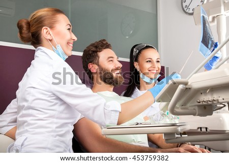 Female doctor and her smiling assistant showing teeth x-ray to male patient in dental hospital. Handsome men with beard sitting in medical chair and looking at the picture.