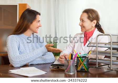 Female doctor and teenage girl patient smiling and examination at table in clinic - stock photo