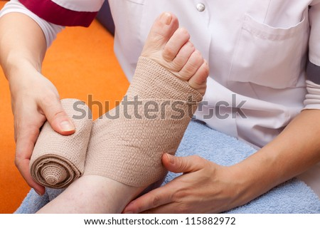 female Doctor bandaged foot of a patient - stock photo