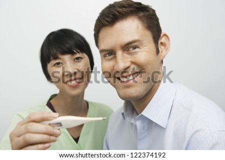 Female doctor checking body temperature of happy patient - stock photo
