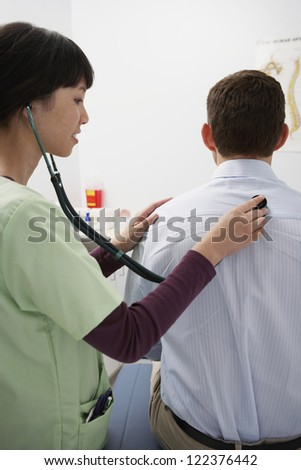 Female doctor checking patient using stethoscope - stock photo