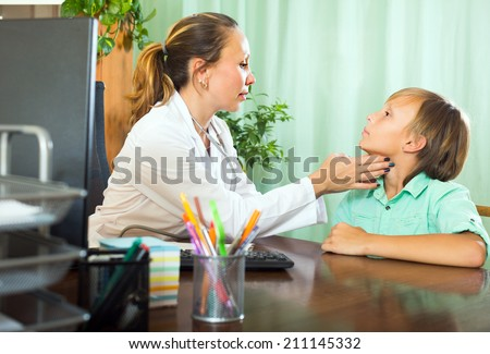 Female doctor checking thyroid of teenage boy patient in clinic  - stock photo