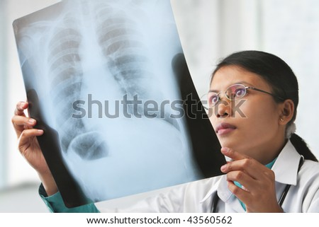 Female doctor checking xray image. focus on the xray image (with some grain or noise from it) - stock photo