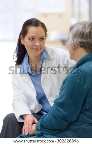 Female doctor comforting senior patient - stock photo
