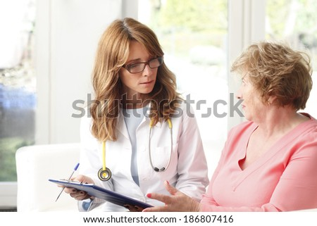 Female doctor consulting with senior patient at small clinic. - stock photo