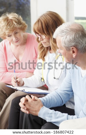 Female doctor consulting with senior patient at small clinic.