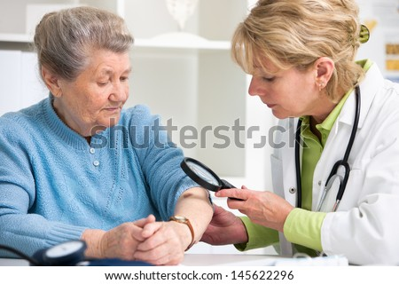 Female doctor examining a mole in the patient - stock photo