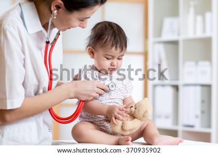 female doctor examining child toddler with stethoscope - stock photo