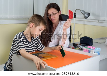 Female Doctor Examining Little Boy's Logical Thinking With Colored Geometric Shapes in Consulting Room - stock photo