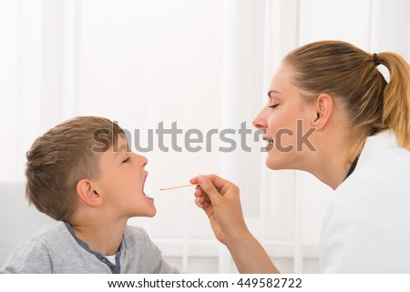 Female Doctor Examining Little Boy's Mouth In Clinic