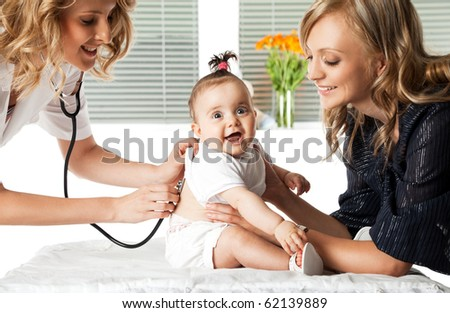 Female doctor examining little smiling baby girl held by her mother - stock photo