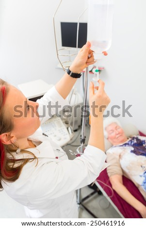 Female doctor giving pensioner in hospital drip infusion